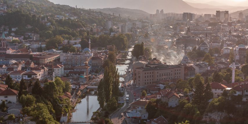 Panoramic aerial cityscape of the historical downtown of Sarajevo timelapse, Bosnia and Herzegovina, with famous buildings and the bridges across Miljacka river before sunset from viewpoint